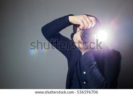Young man takes a picture on a camera with built-in flash. Bright light for illumination of the frame. Royalty-Free Stock Photo #536196706