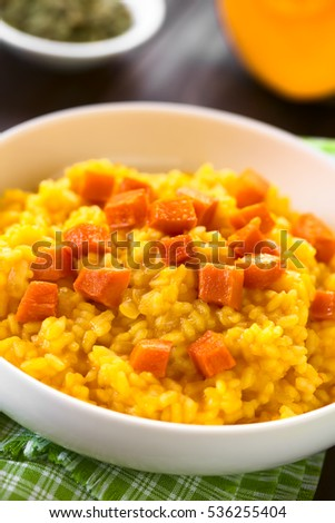 Pumpkin risotto prepared with pumpkin puree, roasted pumpkin pieces on top, photographed with natural light (Selective Focus, Focus one third into the risotto) #536255404