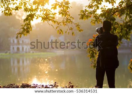December 7, 2016 - Vietnam Traveler man take a photograph in HoanKiem lake in Hanoi #536314531