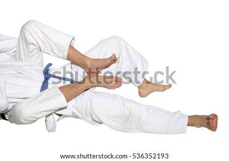 Judo fighters wrestling for supremacy on the white background #536352193