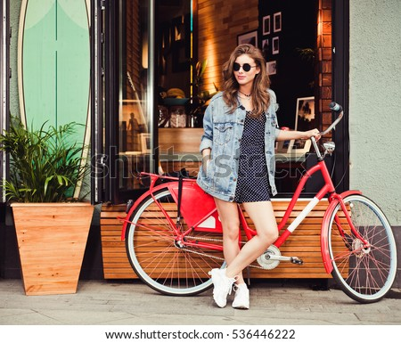 Cute girl in a summer dress, denim jacket, sunglasses stands with red vintage bicycle in a European city. Sunny summer. On background surf cafe.