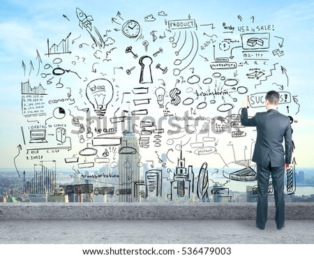 Back view of young man drawing abstract business sketch while standing on concrete rooftop. Success concept #536479003