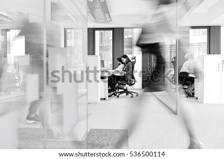 Blurred motion of businesswoman walking with colleagues working in background at office