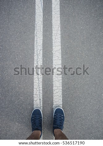 Sport background. man's legs in casual or sport shoes stand on a street road along two white line. foot between couple of line. asphalt textured road. empty copy space for inscription or other objects #536517190
