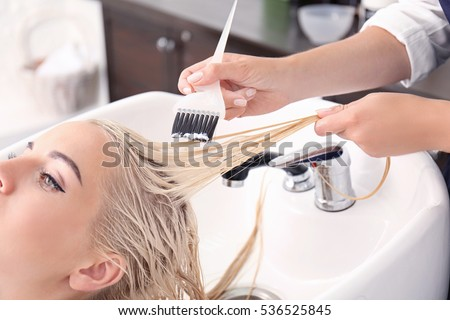 Hairdresser putting mask on woman's hair in salon Royalty-Free Stock Photo #536525845