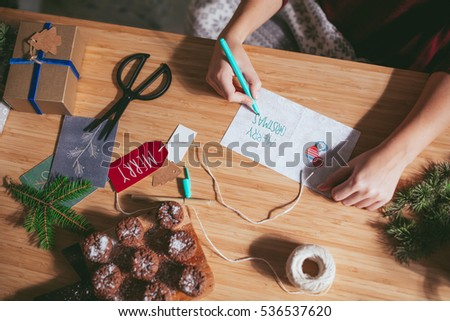Woman Writing Merry Christmas on Card #536537620