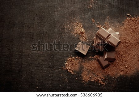 Broken chocolate pieces and cocoa powder on wooden background #536606905