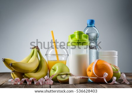 Healthy nutrition in the foreground. Tasty fruits and udeful drinks with a spoon of protein covered by a tape-measure. Nice menu for a diet. #536628403