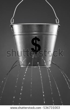 Water leaking from bucket with the concept of finance and losing money #536731003