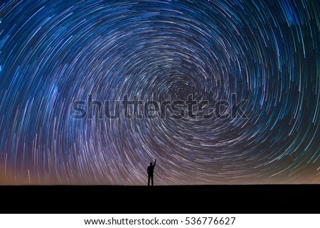 Man Pointing North in a spiral star trail #536776627