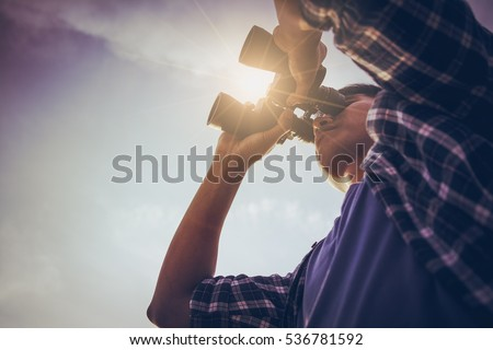 Close-up Of Asian man Hand Holding / looking / watching using Binoculars with copyspace, Technology Binoculars background concept Royalty-Free Stock Photo #536781592