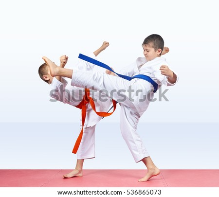 On a red mat two athletes are beating kicks #536865073