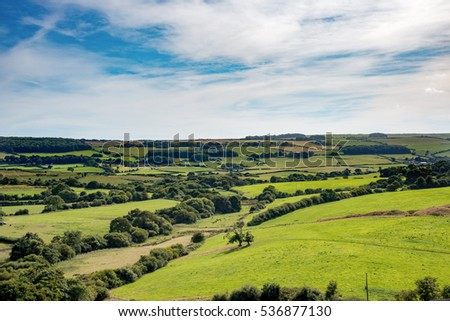 Rolling fields and trees of lush green British countryside stretch to the horizon under wispy clouds and blue sky #536877130