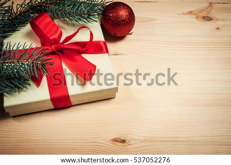 Christmas gift wrapped in red ribbon with fir twig on wooden background