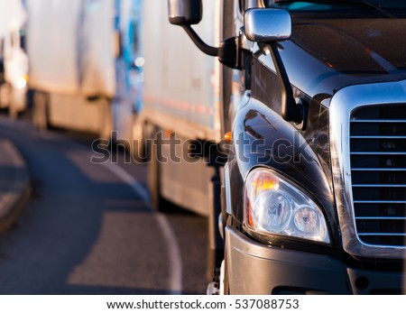 Details of dark semi truck on the road on blured truck and trailer background #537088753