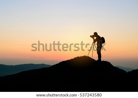silhouette of photographer on top of mountain at sunset background #537243580