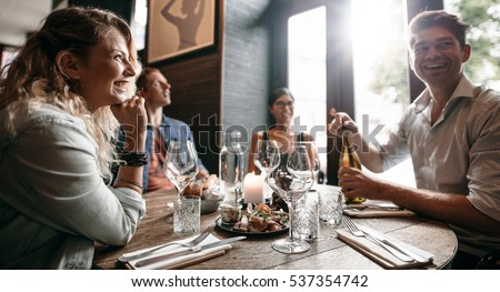 Group of friends enjoying an evening meal with wine at a restaurant. Happy young man and woman having dinner in a restaurant. #537354742