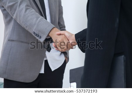 Businessmen's Handshake Partnered with American business woman descent. Confirmation of a business alliance partners as well. Adhering respect,commitment and integrity in business.partnership concepts #537372193