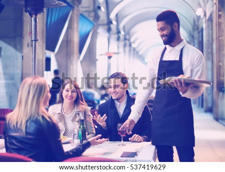positive european afro waiter taking table order and smiling in winter evening #537419629