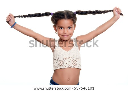 Happy african american small girl smiling and pulling her long braided hair - Isolated on white #537548101