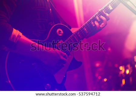 Electric guitar player on a stage with colorful blue and purple scenic illumination, soft selective focus Royalty-Free Stock Photo #537594712