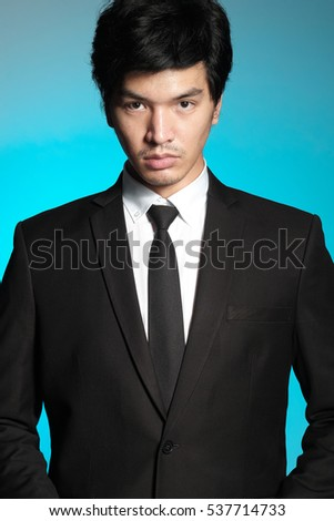 Asian man in black suit and white shirt on blue background #537714733