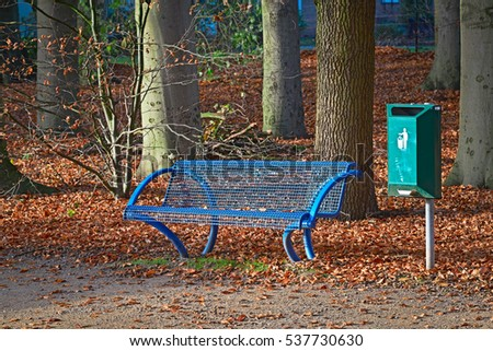 Blue park bench with a green trash can in autumn #537730630