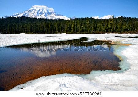 Mount Rainier reflects its snow capped beauty in the clear and still reflection lake which was partly frozen. The shot was taken in early summer at Mount Rainier national park, Washington state. #537730981