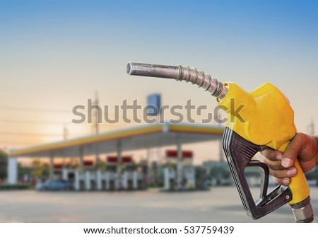 Holding a fuel nozzle against with gas station blurred background. Royalty-Free Stock Photo #537759439