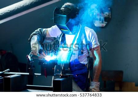 man welding metal in the factory #537764833