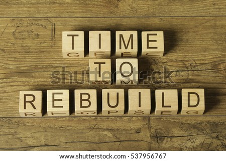 time to rebuild text on wooden cubes on a wooden background Royalty-Free Stock Photo #537956767