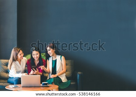 Three beautiful Asian girls using smartphone and laptop, chatting on sofa together at cafe with copy space, modern lifestyle with gadget technology or working woman on casual business concept #538146166