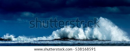 Waves crashing high in front of a blue sky at Coledate in NSW Australia Royalty-Free Stock Photo #538168591