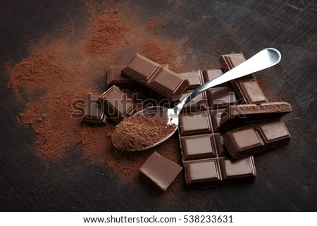 Broken chocolate pieces and spoon with cocoa on wooden background #538233631
