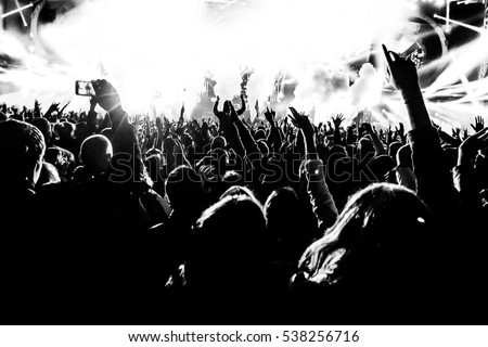 silhouettes of concert crowd in front of bright stage lights #538256716