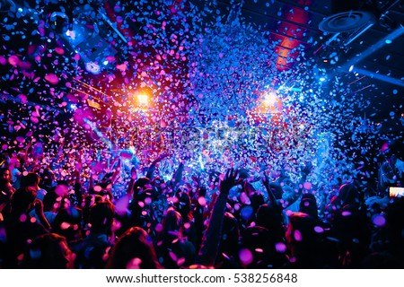 silhouettes of concert crowd in front of bright stage lights and confeti Royalty-Free Stock Photo #538256848