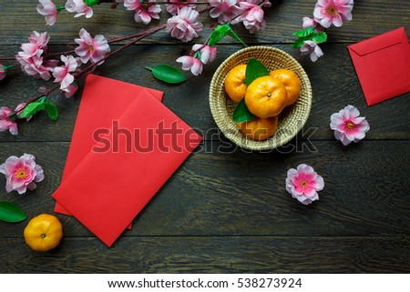 Top view accessories Chinese new year festival decorations.orange,leaf,wood basket,red packet,plum blossom on table wooden background with copy space. Royalty-Free Stock Photo #538273924