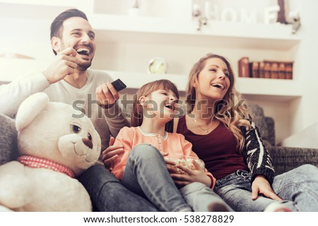 Young family watching TV together at home and having fun together. Royalty-Free Stock Photo #538278829