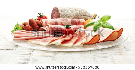 Food tray with delicious salami, pieces of sliced ham, sausage, tomatoes, salad and vegetable - Meat platter with selection - Cutting sausage and cured meat on a celebratory table. #538369888