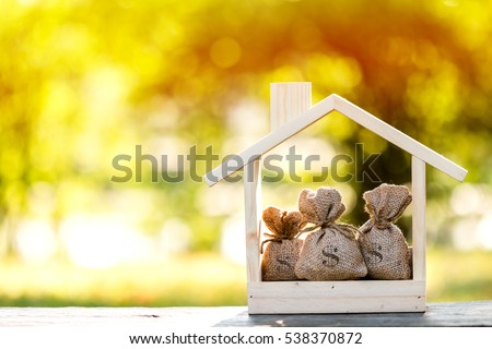 Business loans for real estate concept, a money bags put in a model home on the table on bokeh background in the public park. Royalty-Free Stock Photo #538370872