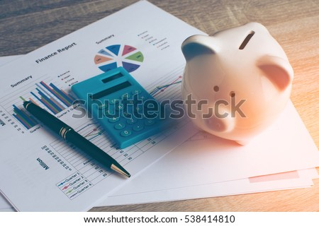 Piggy bank with business stuff, business and finance concept, vintage color tone. Royalty-Free Stock Photo #538414810