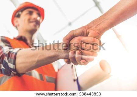 Handsome construction workers in protective helmets and vests are shaking hands while working in the office center Royalty-Free Stock Photo #538443850