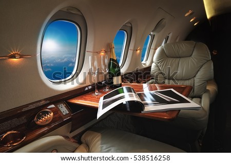 luxury interior in the modern  business jet and sunlight at the window/sky and clouds through the porthole #538516258