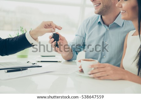 Close up photo of broker giving keys of new house to happy couple.