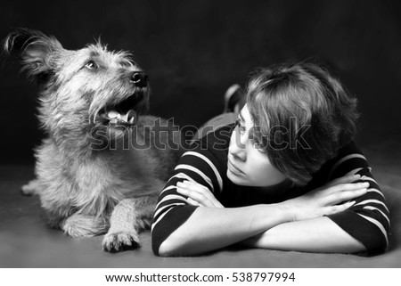 Portrait of a beautiful young woman with a funny shaggy dog on a dark background. High quality, photographed in the studio.