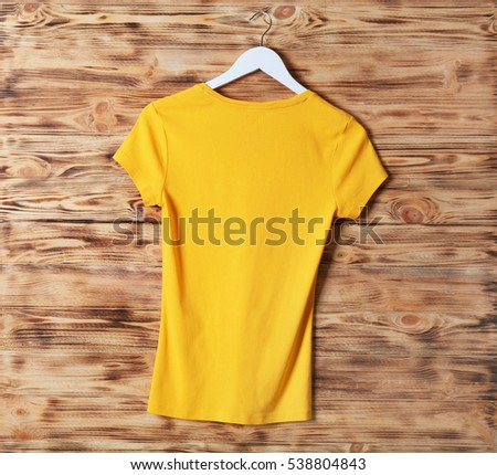 Blank yellow t-shirt against wooden background #538804843