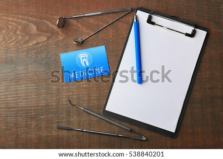 Business card, clipboard and dental tools on wooden background. Medical service concept