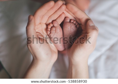 Parent holding in the hands feet of newborn baby. #538858930