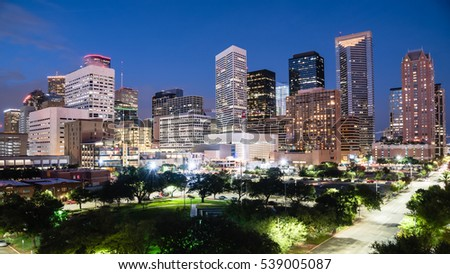 Aerial view downtown Houston illuminated at blue hour with green city park and modern skylines light. The most populous city in Texas, fourth-most in US. Architecture and travel background. Panorama.