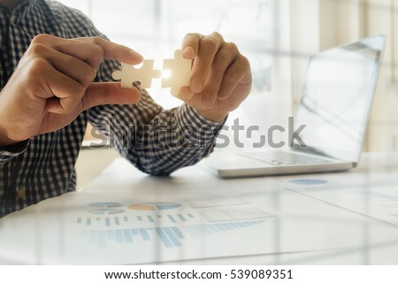 Business man hands connecting jigsaw puzzle. Business solutions, success and strategy concept. Close up photo with selective focus.